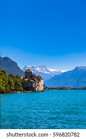 Beautiful view of Chillon castle on the lake side of Geneva lake, with the peaks Dents du Midi of Swiss Alps in background, Montreux, Canton of Vaud, Switzerland