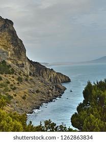 Beautiful view from cliff, cape Kapchik on Black Sea, rocks, stones, green juniper trees, dry grass, gray sky and gray-blue sea, Crimea
