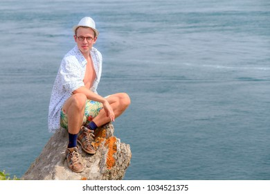 Beautiful view of a colorful young tourist on the rocks at Pointe du Grouin near Cancale in Brittany, France,  in summer
