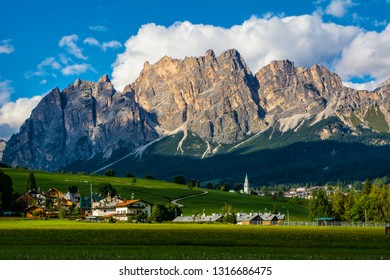 Beautiful view of Cortina d'Ampezzo town with alpine green landscape and massive Dolomites Alps in the background.