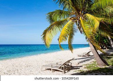 beautiful view at empty tropical island at fiji with white sand beach, sunbeds, palm trees and turquoise lagoon, copy space on left