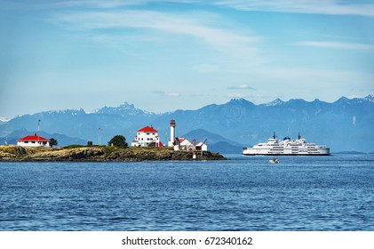 Beautiful view of Entrance island Lighthouse with BC Ferries passenger ship Queen of Alberni.  Photo taken on 2017.07.04 at Gabriola Island BC Canada.