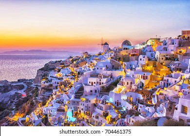 Beautiful view of fabulous picturesque village of Oia with traditional white houses and windmills in Santorini island at night, Greece