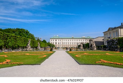 "Beautiful view of famous baroque park ""Mirabell Garden"" (Mirabellgarten - public place). Green flowerbed with walkways in park under bright blue sky, Salzburg"