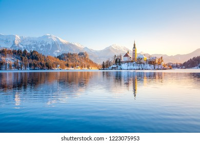 Beautiful view of famous Bled Island at scenic Lake Bled with Bled Castle and Julian Alps in the background in golden morning light at sunrise in winter, Slovenia.