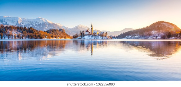 Beautiful view of famous Bled Island (Blejski otok) at scenic Lake Bled with Bled Castle (Blejski grad) and Julian Alps in the background in golden morning light at sunrise in winter, Slovenia