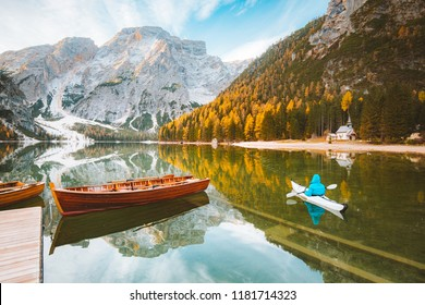 Beautiful view of famous Lago di Braies with traditonal rowing boat and young man in kayak at sunrise in fall, Dolomites, Italy