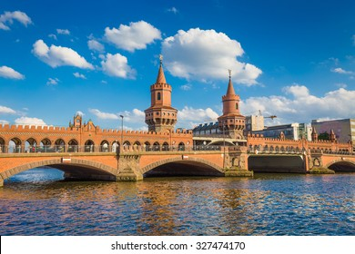 Beautiful view of famous Oberbaum Bridge crossing the Spree river on a sunny day with blue sky and clouds in summer, Berlin Friedrichshain-Kreuzberg, Germany
