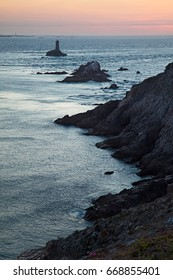 Beautiful view of famous Phare of Pointe du Raz on Cape Sizun at sunset in summer, Brittany, northern France - cold filter color at the end of light