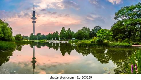 Beautiful view of flower garden in Planten um Blomen park with famous Heinrich-Hertz-Turm radio telecommunication tower in the background at dusk, Hamburg, Germany