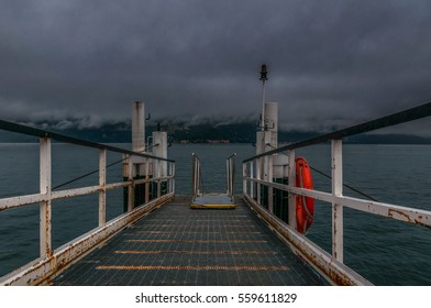 Beautiful view of the foggy lake Como through the old pier.