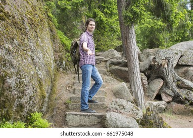 Beautiful view in the forest with a young attractive man standing on stone stairs.