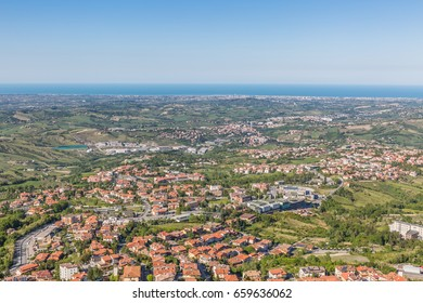 beautiful view from the fortress tower of San Marino: green valley, majestic blue sea translating in sky in sunny spring day