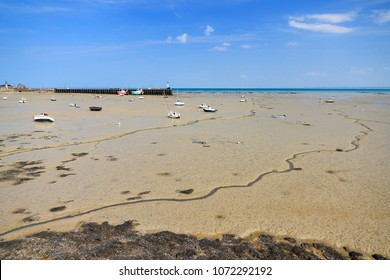 Beautiful view of the French beach at low tide with boats on dry land in Cancale, France, in summer