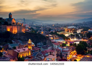 Beautiful view of the Georgian capital Tbilisi at sunset Narikala fortress in the foreground, Kura river with a bridge and mountains in the background.