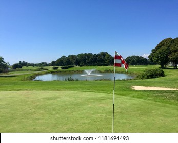 Beautiful view of golf course green hole flag on a bright sunny summer day. Lake with fountain in background water hazard in middle of fairway for player challenge