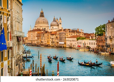 Beautiful view of Gondolas on famous Canal Grande with Basilica di Santa Maria della Salute in golden evening light at sunset in Venice, Italy