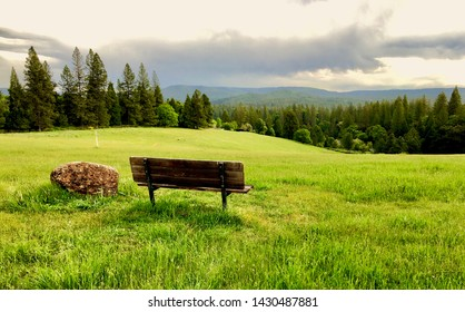 Beautiful view of a grassy field up in the mountains with park bench
