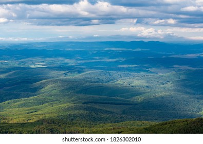 Beautiful view of green hills from above with clouds. Summer landscape from Galyatető Mountain in the Mátra Mountain.
