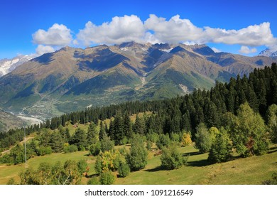 Beautiful view of a green valley covered with forest, mountain peaks of the Caucasus mountains and clouds