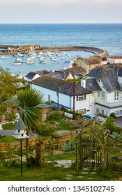 The beautiful view from the high Cobb road to the famous man-made Cobb harbor of Lyme Regis with the docked boats and yachts. West Dorset. England