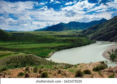 Beautiful view from hill to the confluence of two rivers under a blue sky with clouds in the Altai mountains. Amazing landscape of green valley on a sunny summer day.