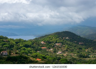 Beautiful view of the hills and the sea lagoon under a cloudy sky on Elba Island in Tuscany, Italy