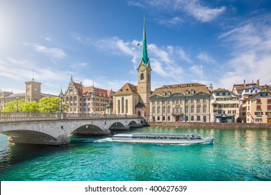 Beautiful view of the historic city center of Zurich with famous Fraumunster Church and excursion boat on river Limmat on a sunny day with blue sky, Canton of Zurich, Switzerland
