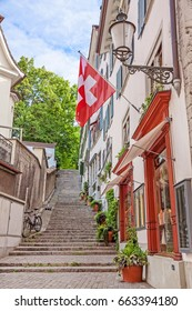 Beautiful view of historic city center of Zurich with Swiss flags at buildings on a sunny day in summer, Switzerland