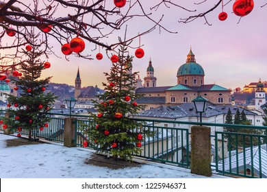 Beautiful view of the historic city of Salzburg with famous Salzburg Cathedral in winter, Austria.Christmas trees with red Christmas balls against the background of the winter Salzburg.