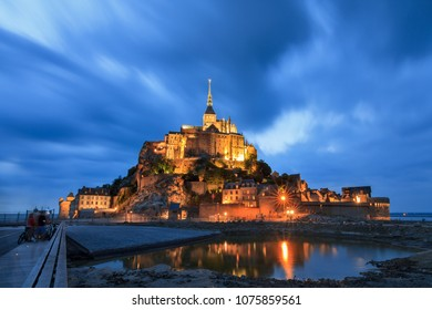 Beautiful view of historic landmark Le Mont Saint-Michel in Normandy, France, a famous UNESCO world heritage site and tourist attraction, at twilight in the blue hour after sunset