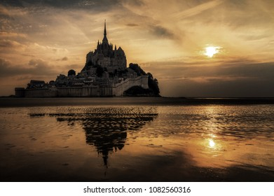 Beautiful view of historic landmark Le Mont Saint-Michel in Normandy, France, a famous UNESCO world heritage site and tourist attraction, at sunset