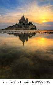 Beautiful view of historic landmark Le Mont Saint-Michel in Normandy, France, a famous UNESCO world heritage site and tourist attraction, at sunset with reflection
