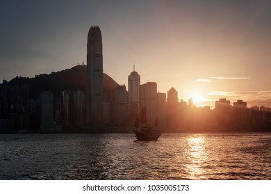 Beautiful view of the Hong Kong Island skyline at sunset. Skyscrapers in downtown and traditional Chinese sailing ship in Victoria harbor. Hong Kong is a popular tourist destination of Asia.