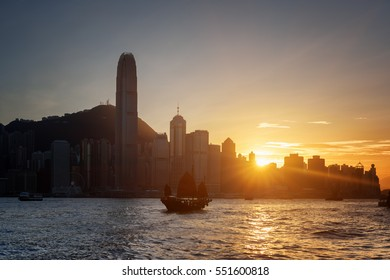 Beautiful view of the Hong Kong Island skyline at sunset. Skyscrapers in downtown of Hong Kong are visible from Kowloon side. Tourists on traditional Chinese sailing ship crosses Victoria harbor.