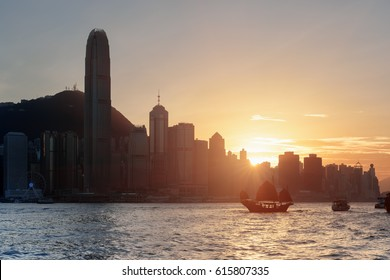 Beautiful view of the Hong Kong Island skyline at sunset. Skyscrapers in downtown of Hong Kong are visible from Kowloon side. Tourist boats and traditional Chinese sailing ship in Victoria harbor.