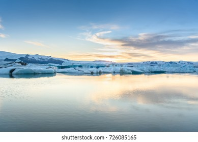 Beautiful view of icebergs in Jokulsarlon glacier lagoon at sunset, Iceland, global warming concept, selective focus