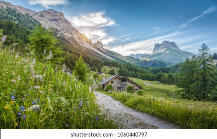 Beautiful view of idyllic alpine mountain scenery with traditional old mountain chalets and fresh green meadows on a sunny day with blue sky and clouds in springtime, South Tyrol, Italy