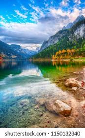 Beautiful view of idyllic colorful autumn scenery with Dachstein mountain summit by Gosausee mountain lake in fall Salzkammergut region Upper Austria Austria