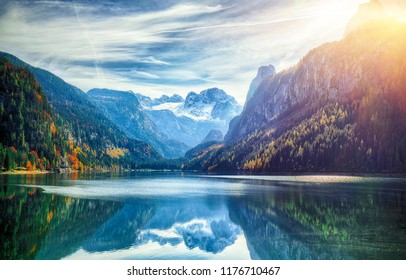 Beautiful view of idyllic colorful autumn scenery with Dachstein mountain summit reflecting in crystal clear Gosausee mountain lake in fall. Salzkammergut region Upper Austria