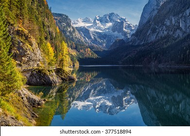 Beautiful view of idyllic colorful autumn scenery with Dachstein mountain summit reflecting in crystal clear Gosausee mountain lake in fall, Salzkammergut region, Upper Austria, Austria