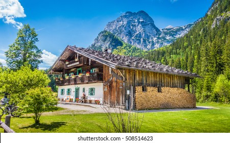 Beautiful view of idyllic mountain scenery in the Alps with traditional farmhouse and fresh green mountain pastures with blooming flowers on a sunny day with blue sky and clouds in summer