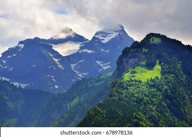 Beautiful view of idyllic mountain scenery in the Alps with snow covered mountain peaks and green alpine meadows in Uri canton nearby Altdorf city, Switzerland