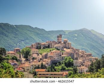 Beautiful view of idyllic village Castel del Monte, set into a steep hillside under apennine mountain peaks on a sunny summer day, Gran Sasso e Monti della Laga National Park, L'Aquila, Abruzzo, Italy