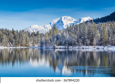 Beautiful view of idyllic winter wonderland with crystal clear mountain lake in the Alps on a cold sunny day with blue sky and clouds, Nationalpark Berchtesgadener Land, Upper Bavaria, Germany