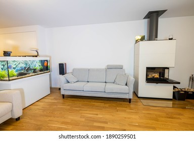 Beautiful view of interior of modern living room. White fireplace, big aquarium with colorful fishes and light colored furniture on white wall background.