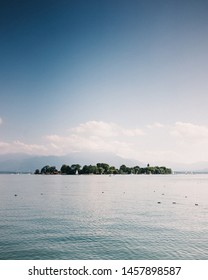 Beautiful view of island on blue lake Chiemsee against spectacular mountains and sky during sunny day
