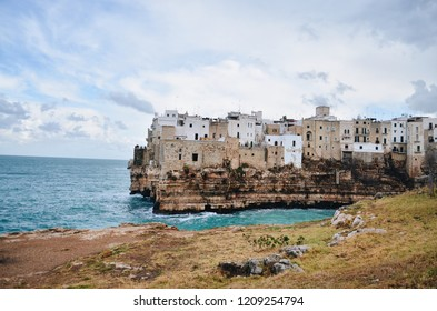 Beautiful view of Italian old-town Polignano a Mare in winter. White houses on the cliffs of crystal blue sea. Puglia region Italy, coastline view of historical town on the seaside of adriatic sea
