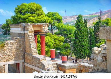 Beautiful view from Knossos Palace, Heraklion, Crete, Southern Greece. Ancient ruins of the Minoan civilization with famous red pillars at the background of green trees, mountain slope and blue sky