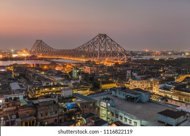 Beautiful view of Kolkata city with a Howrah bridge on the river Hooghly at twilight.